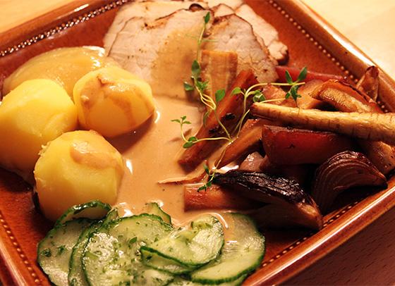 Helstekt kotlettrad i skivor, serverad med ugnsrostade rotfrukter och äpplen, kokt potatis, pressgurka, sås och äppelmos.